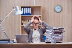 La secrétaire stressante occupée de femme sous l'effort dans le bureau photographie stock