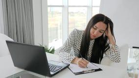 La secretaria arruga los documentos, encargado hermoso que las impresiones mandan un SMS en el ordenador portátil en el escritori metrajes