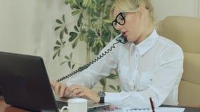 La secretaria atractiva está mecanografiando en el teclado y almacen de metraje de vídeo