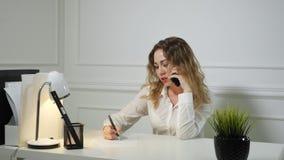La secretaria de la mujer joven est? hablando en el tel?fono m?vil y est? tomando notas Concepto de trabajo de la oficina metrajes