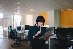 La secretaria elegante y hermosa joven revisa los papeles Contra el contexto de una oficina hermosa fotos de archivo