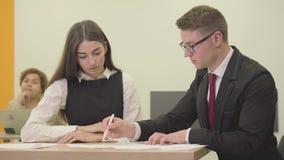 La secretaria joven que se sienta con su jefe en la oficina El hombre que corrige el informe de la muchacha Vida de la oficina almacen de video