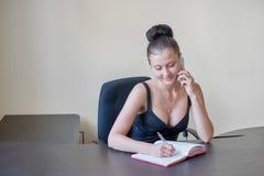 La secretaria ocupada está contestando a llamada y está escribiendo la nota al mismo tiempo foto de archivo libre de regalías