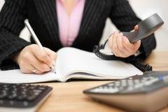 La secretaria ocupada está contestando a llamada y está escribiendo la nota Imagenes de archivo
