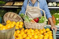 La section médiane de l'homme tenant les oranges proches calent avec le panier végétal dans le supermarché photographie stock libre de droits
