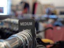 La section moyenne se connectent le support en acier d'habillement avec des cintres dans le magasin photographie stock
