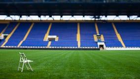 La sedia bianca sola sul campo dello stadio Fotografie Stock