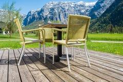 La sedia del cortile sul pavimento di legno con le alpi delle montagne alza il backgro verticalmente Fotografie Stock Libere da Diritti