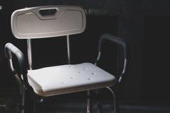 La sedia di bagno di plastica per l'inondazione dei disabili o dell'anziano messa nella luce lasciante scura viene dalla parte di immagine stock