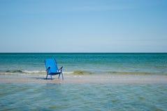 La sedia di spiaggia blu sul bianco del cielo blu della spiaggia si appanna l'estate fotografie stock libere da diritti