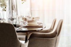 La sedia pranzante piacevole alta chiusa con la tavola ed il piatto di legno mette il inte Fotografie Stock