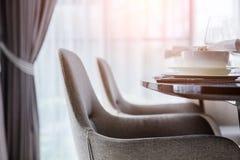 La sedia pranzante piacevole alta chiusa con la tavola ed il piatto di legno mette il inte Fotografia Stock