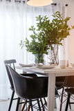 La sedia pranzante piacevole alta chiusa con la tavola ed il piatto di legno mette il inte Fotografie Stock Libere da Diritti