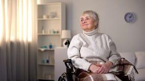 La sedia a rotelle di seduta femminile anziana sorridente ha coperto il paziente generale e felice della clinica immagine stock