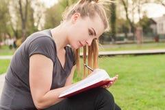 La seduta attraente della donna all'aperto e scrive nel suo jour personale fotografia stock libera da diritti