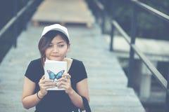 La seduta dell'adolescente della donna gode del libro di lettura Immagine Stock