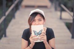 La seduta dell'adolescente della donna gode del libro di lettura Fotografie Stock