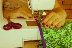 La seduta della cucitrice della donna e cuce sulla macchina per cucire dressmaker immagini stock