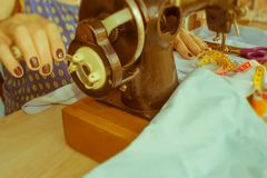 La seduta della cucitrice della donna e cuce sulla macchina per cucire dressmaker fotografia stock libera da diritti