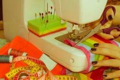 La seduta della cucitrice della donna e cuce sulla macchina per cucire dressmaker fotografia stock