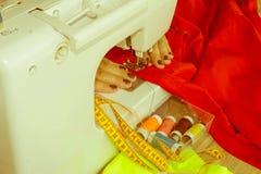 La seduta della cucitrice della donna e cuce sulla macchina per cucire dressmaker immagine stock libera da diritti