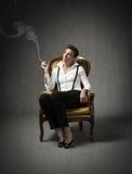La seduta della donna e fuma immagine stock libera da diritti