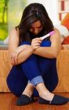 La seduta della donna e la gravidanza castane abbastanza giovani della tenuta si dirigono la prova, testa di curvatura giù, fondo Fotografia Stock