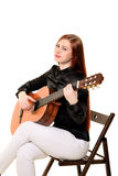 La seduta della giovane donna posa nello studio che tiene un guit classico Immagini Stock