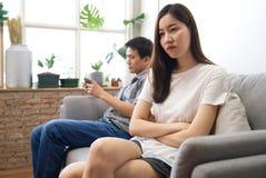 La seduta della ragazza sul sofà sta ritenendo arrabbiato il suo ragazzo fotografia stock libera da diritti