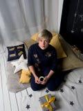 La seduta di seduta della donna sui cuscini con un regalo sta bevendo il caffè caldo immagine stock libera da diritti