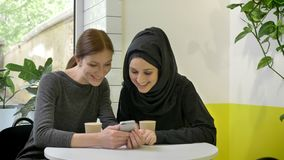 La seduta di due giovani donne graziose in caffè, uno di loro donna musulmana nel hijab, esaminante telefono e ridente, sorpresa archivi video