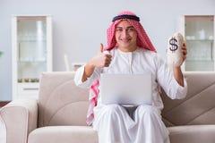 La seduta di lavoro dell'uomo d'affari arabo allo strato Immagine Stock