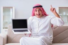 La seduta di lavoro dell'uomo d'affari arabo allo strato Fotografia Stock