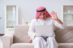 La seduta di lavoro dell'uomo d'affari arabo allo strato Immagini Stock