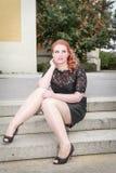 La seduta di peso eccessivo della donna si è vestita nel nero su una scala fotografia stock libera da diritti