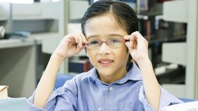 La seduta sveglia divertente sorridente del ragazzo e tiene gli occhiali sul fac Fotografia Stock Libera da Diritti