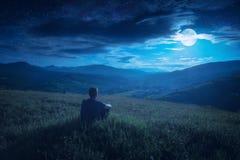 La seduta umana su una collina dentro e gode dell'aumento della luna Fotografia Stock Libera da Diritti