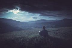 La seduta umana su una collina dentro e gode dell'aumento della luna Styl di Instagram Immagini Stock Libere da Diritti