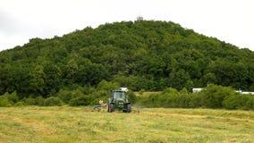 La segadora grande está dando vuelta sobre la hierba seca, camión con el fabricante del heno que trabaja en el prado en tierras d almacen de metraje de vídeo