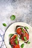 La segale tosta con formaggio a pasta molle, il pomodoro, la cipolla rossa ed i capperi principale vi immagine stock