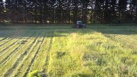 la Segar-máquina da vuelta al surco siguiente del campo para cortar la hierba del heno almacen de metraje de vídeo