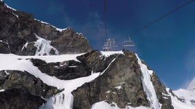 La seggiovia aumenta fino alla cima della montagna con le rocce nella stazione sciistica dell'inverno video d archivio