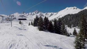 La seggiovia aumenta fino alla cima della montagna nella stazione sciistica dell'inverno nel giorno soleggiato stock footage