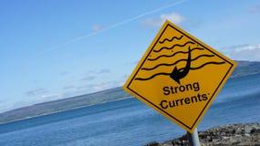 La segnaletica di sicurezza gialla dell'acqua che dichiara là è forti correnti Fotografie Stock