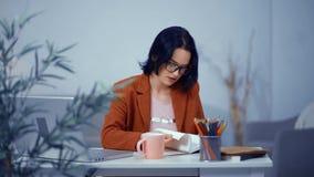 La segretaria ? occupata con le mansioni di ogni giorno sul posto di lavoro La donna gira le pagine stock footage