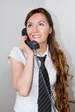La segretaria graziosa comunica con il telefono in ufficio Fotografia Stock