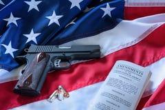 La segunda enmienda y control de armas en los E.E.U.U., concepto Una arma de mano, balas, y la constitución americana en la bande foto de archivo