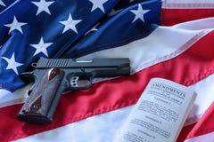 La segunda enmienda y control de armas en los E.E.U.U., concepto Una arma de mano y la constitución americana en la bandera de lo imagen de archivo libre de regalías