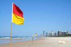 La seguridad de la natación señala Gold Coast por medio de una bandera Imagen de archivo libre de regalías