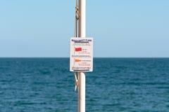 La seguridad de la playa señala la muestra por medio de una bandera Fotos de archivo